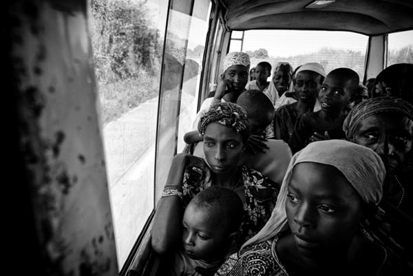 """Des rescapés centrafricains à peine arrivés à la ville frontière de Garoua-Boulaï au Cameroun sont transférés par la Croix Rouge camerounaise, le 30 octobre 2014, vers le camp de réfugiés de Gado à une vingtaine de kilomètres de là.<br /> La tension est palpable sur les visages. Après des mois d'errance dans la brousse pour échapper à leurs assaillants, ces nouveaux exilés pensent déjà à ce qu'ils vont devenir. L'une d'entre eux, la tête collée à la vitre, dira au moment où le bus entame sa traversée du camp : """"c'est donc ça des réfugiés ?"""""""